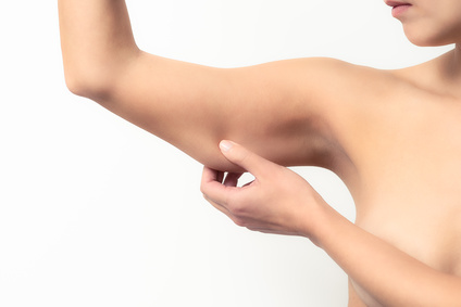 Frau prft den schlaffen Muskel an ihrem Arm